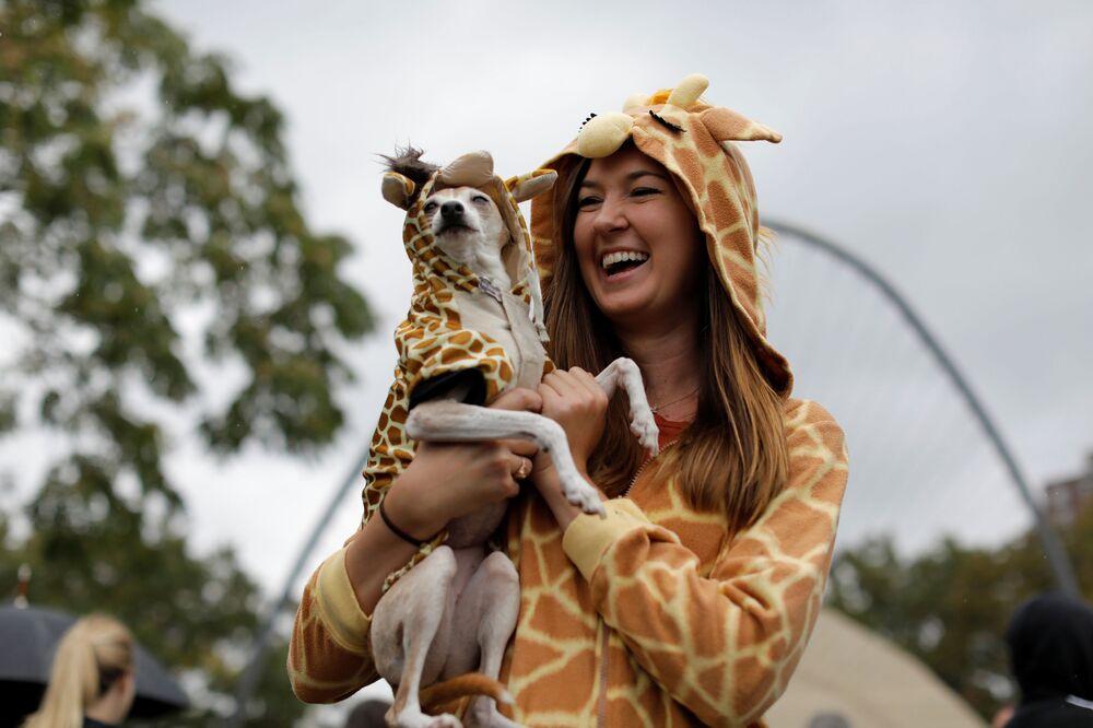 Marcie Walker con il suo cane Nana vestiti da giraffa all'annuale Halloween Dog Parade a New York