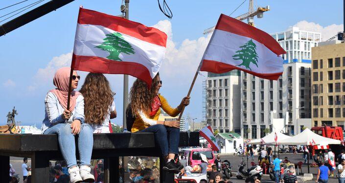 Ragazze sventolano le bandiere libanesi in piazza dei Martiri a Beirut
