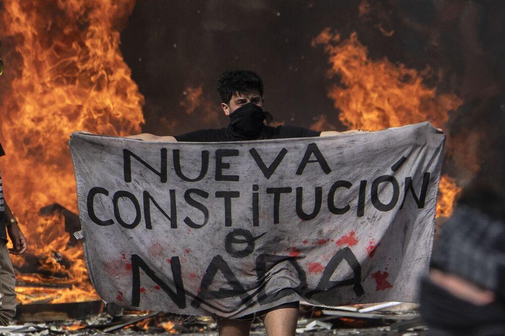 Un manifestante tiene in mano un pezzo di stoffa con la scritta Nuova Costituzione o niente durante le proteste in Piazza Italia a Santiago il 22 ottobre 2019, Cile