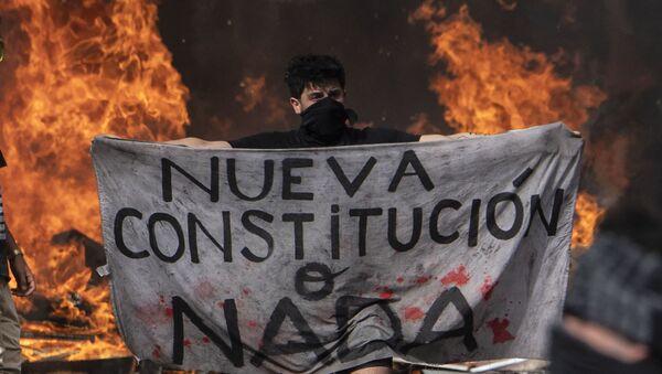 Un manifestante tiene in mano un pezzo di stoffa con la scritta Nuova Costituzione o niente durante le proteste in Piazza Italia a Santiago il 22 ottobre 2019, Cile  - Sputnik Italia