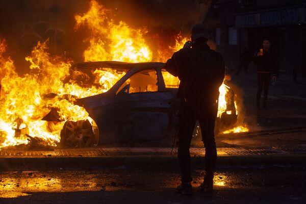 L'uomo scatta le foto di un'auto in fiamme durante le violente proteste a Santiago, il 19 ottobre 2019.  - Sputnik Italia