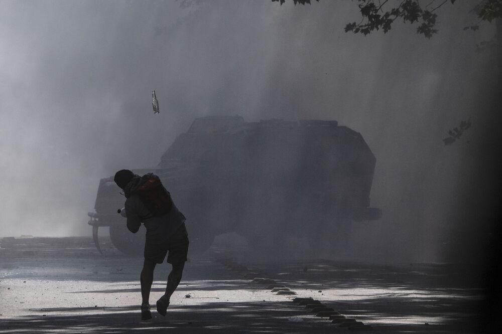 Un manifestante lancia una bottiglia ad un mezzo della polizia durante le proteste in Piazza Italia a Santiago il 22 ottobre 2019, Cile