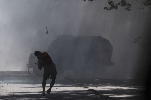 Un manifestante lancia una bottiglia ad un mezzo della polizia durante le proteste in Piazza Italia a Santiago il 22 ottobre 2019, Cile - Sputnik Italia