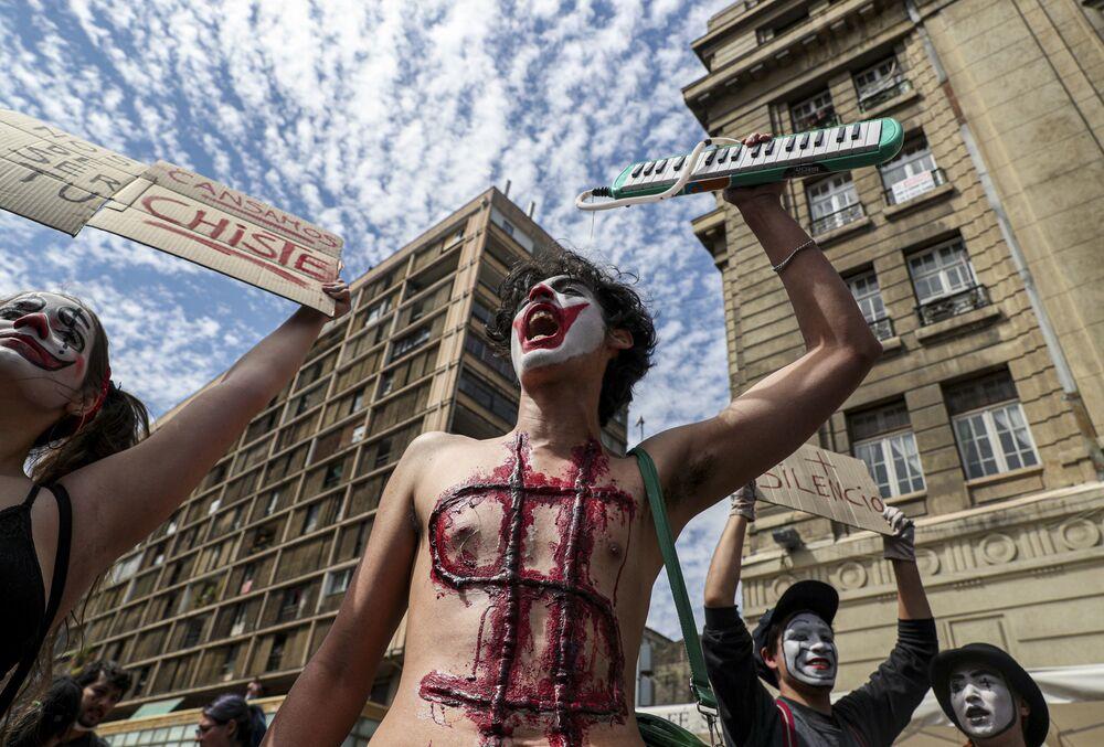 I manifestanti mascherati da clown durante le proteste in Piazza Italia a Santiago il 23 ottobre 2019, Cile
