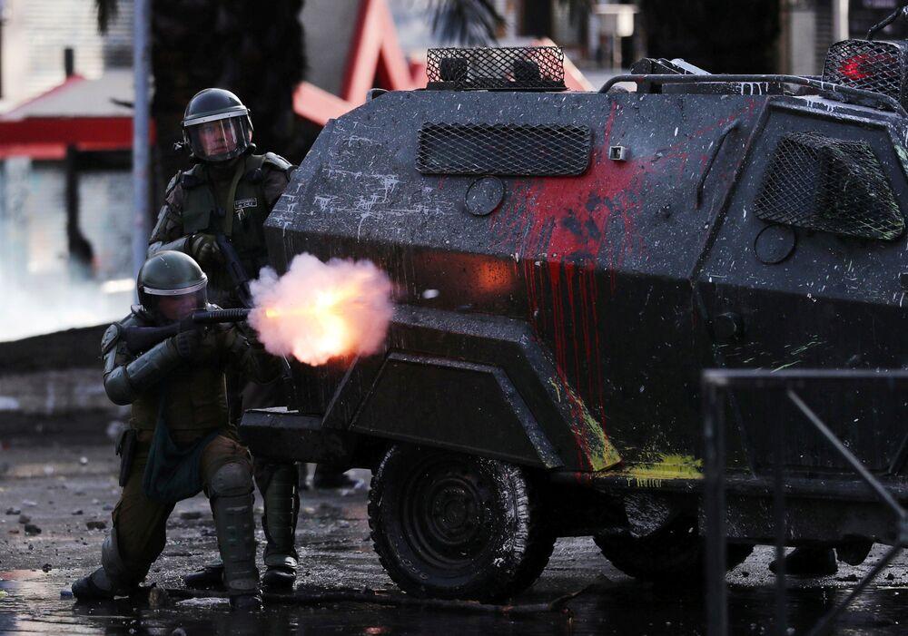 Un poliziotto spara lacrimogeni contro i manifestanti che protestano contro il modello economico statale del Cile a Santiago, Cile, 22 ottobre 2019.
