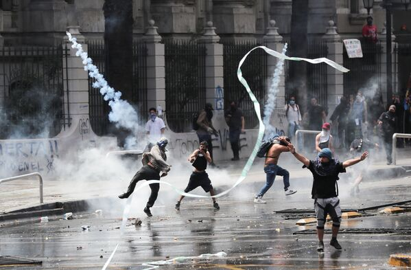 Un manifestante lancia una bomboletta di gas lacrimogeni durante le proteste in Piazza Italia a Santiago il 23 ottobre 2019, Cile - Sputnik Italia
