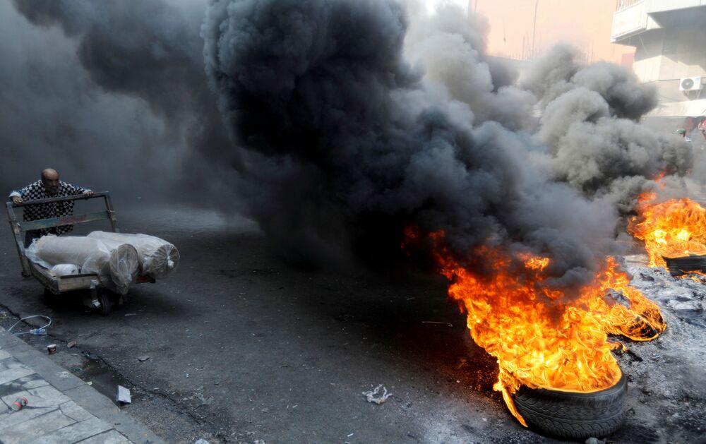 Manifestanti iracheni bruciano delle gomme mentre bloccano la strada durante le proteste antigovernative a Baghdad (Iraq), il 3 novembre 2019