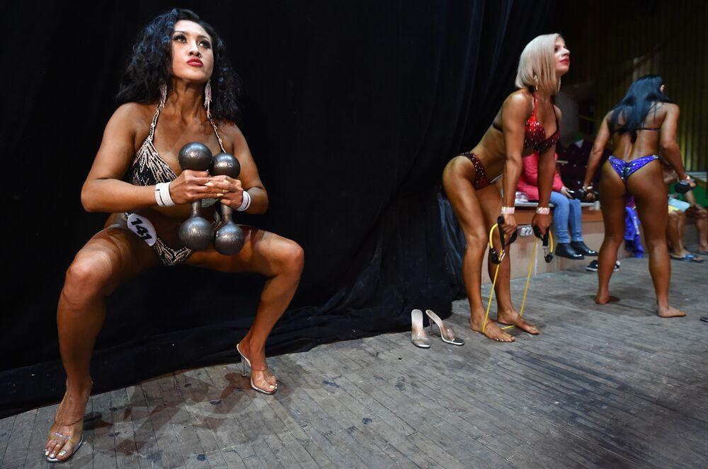 Le bodybuilder donne si riscaldano prima di salire sul palco durante il concorso di bodybuilding Bikini Fitness a Bishkek