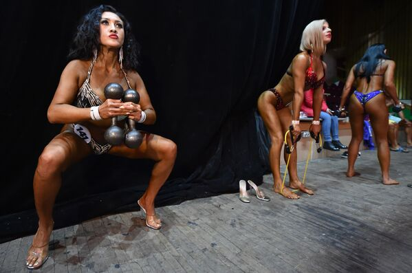Le bodybuilder donne si riscaldano prima di salire sul palco durante il concorso di bodybuilding Bikini Fitness a Bishkek  - Sputnik Italia
