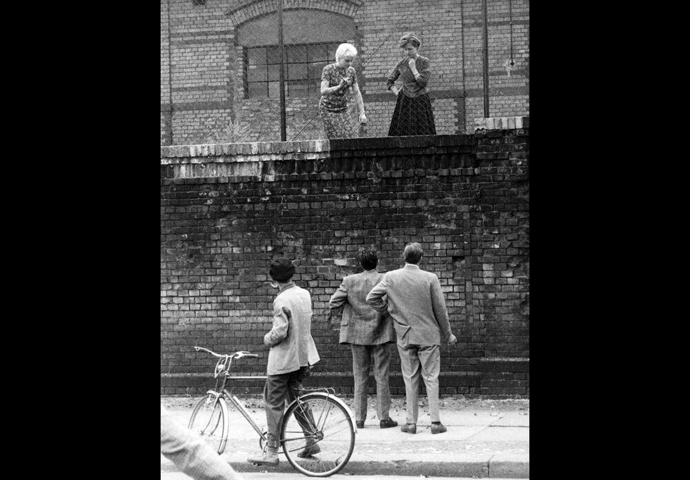 Uomini sul lato ovest del muro di Berlino che parlano con le loro ragazze dietro un recinto alla stazione ferroviaria della Stettiner Bahnhof