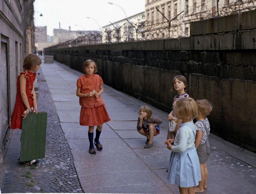 Bambini vicino al muro di Berlino su Heinrich-Heine-Strasse nel 1968