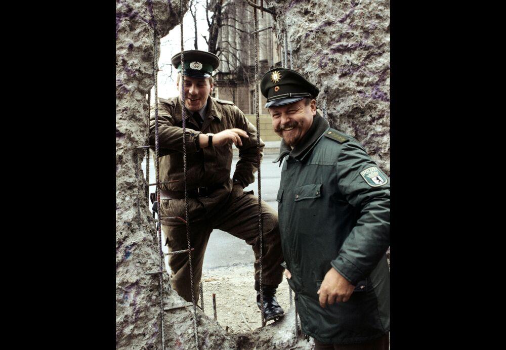 Guardie di frontiera delle due Germanie danvati al muro di Berlino