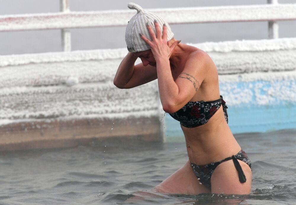 Una donna, membro del centro di nuoto nell'acqua gelata Megapolus, si prepara alle gare invernali nel fiume Enisej a Krasnoyarsk, Siberia.