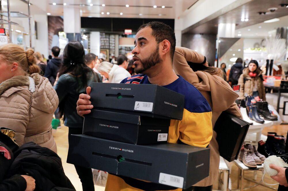 Quanto lavoro per i dipendenti! Un commesso del negozio Macy's a New York si affretta a soddisfare le esigenze dei clienti