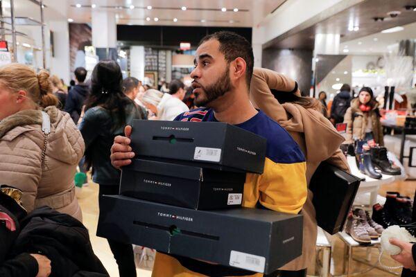 Quanto lavoro per i dipendenti! Un commesso del negozio Macy's a New York si affretta a soddisfare le esigenze dei clienti - Sputnik Italia