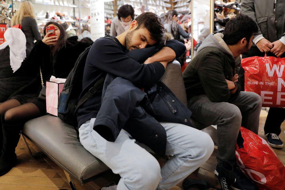 Un uomo si fa un bel sonnellino mentre aspetta la moglie nel negozio Macy's a New York