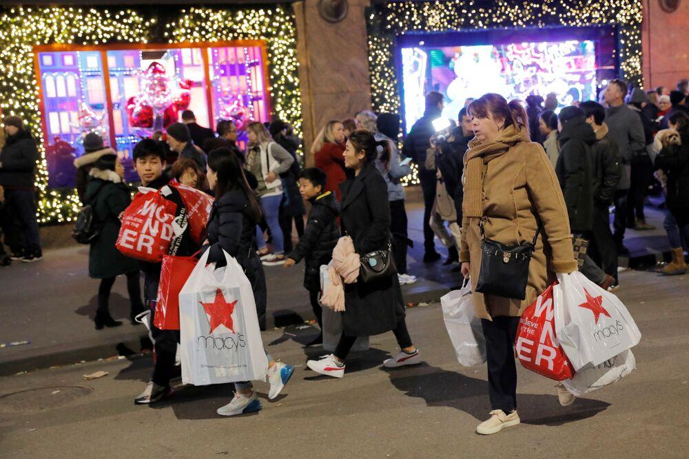 Gente esce con i propri acquisti dal negozio Macy's nel Black Friday a New York, USA