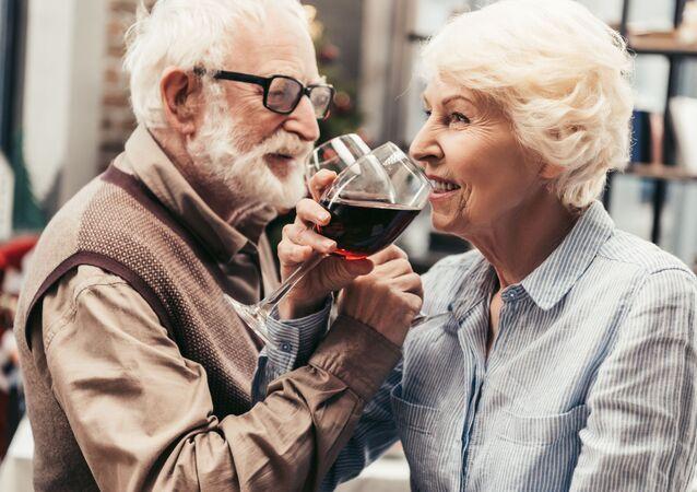 Coppia di anziani beve bicchiere di vino