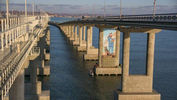 Il disegno di un operaio con un gatto tra due piloni del Ponte di Crimea - Sputnik Italia
