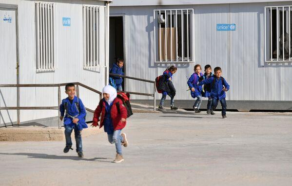 Dei bambini escono dalla scuola nel campo profughi di Kharzholi vicino a Damasco - Sputnik Italia