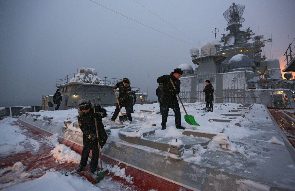 I marinai spazzano la neve dai sili di lancio del complesso missilistico Granit all'incrociatore Pyotr Velikiy.