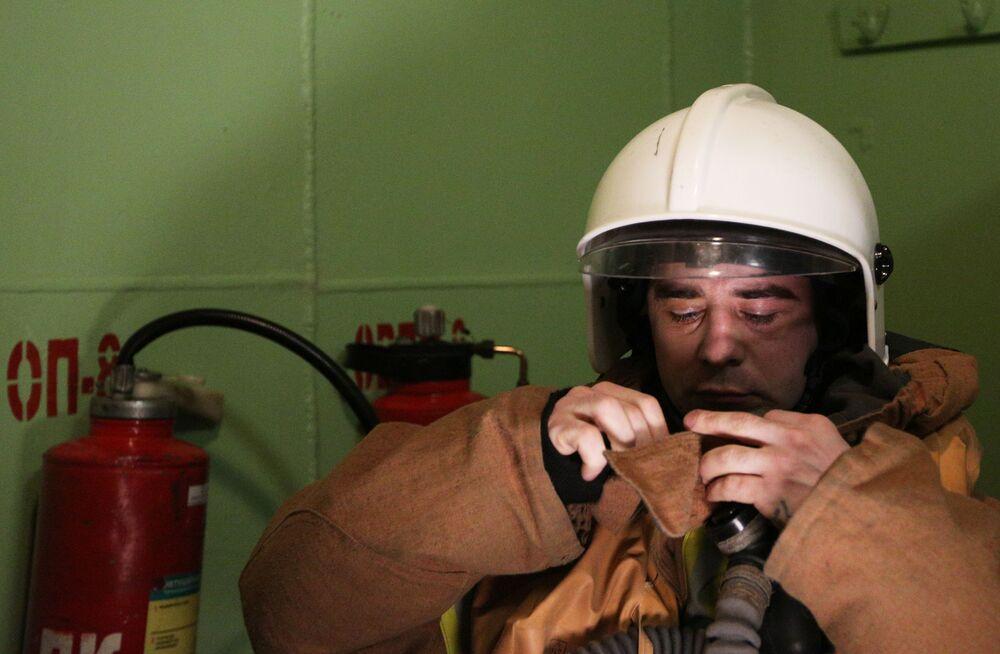 Un pompiere si mette la maschera antigas durante l'addestramento a bordo dell'incrociatore Pyotr Velikiy.