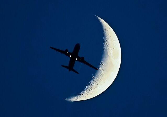 La sagoma di un aereo in volo con la Luna sullo sfondo