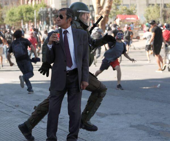 Un uomo beve la coca cola durante le proteste a Santiago del Cile. - Sputnik Italia