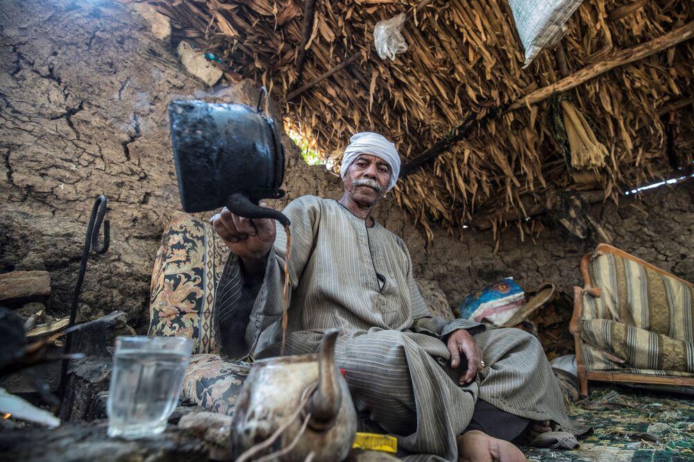 Ramadan Kamel, un contadino egiziano di 71 anni, prepara il tè mentre riposa in una baracca vicino al suo terreno agricolo nel villaggio di Baharmis, nei pressi di Cairo.