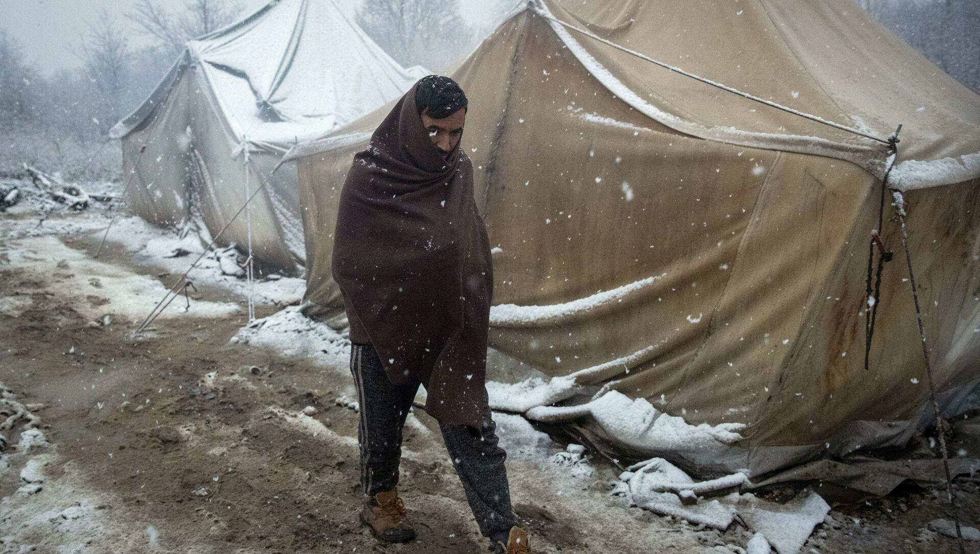 Беженец, идущий по лагерю в Боснии - Sputnik Italia, 1920, 01.02.2021