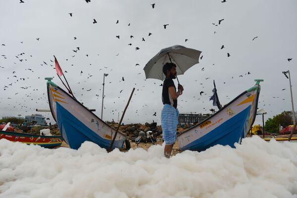 Un uomo su una spiaggia coperta da schiuma tossica in India. - Sputnik Italia