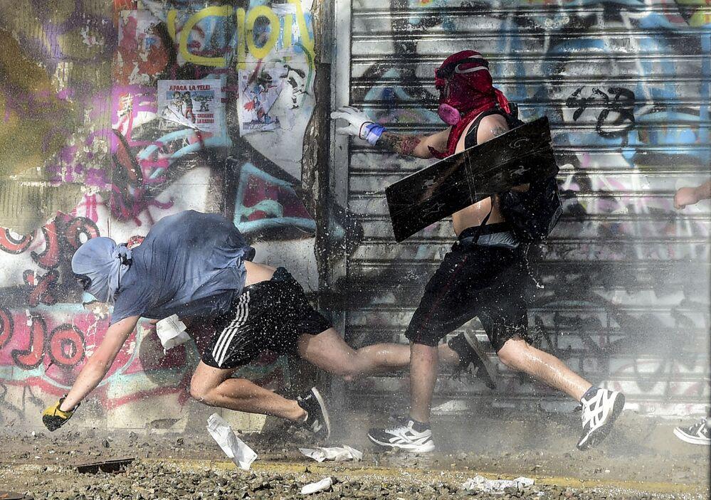 Un manifestante cade mentre lui ed altri fuggono dalla polizia in assetto antisommossa durante una protesta contro il governo del presidente cileno Sebastian Pinera a Santiago, il 6 dicembre 2019