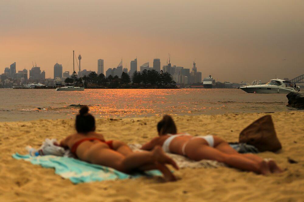 Delle ragazze sulla Milk Beach con all'orizzonte il fumo degli incendi boschivi a Sydney, in Australia, il 7 dicembre 2019
