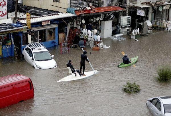 Cittadini libanesi usano una tavola da surf come mezzo di trasporto per una strada allagata a causa delle forti pioggi a Beirut, il 9 dicembre 2019 - Sputnik Italia