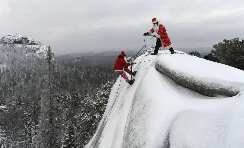 I membri della squadra di ricerca e soccorso in un costume di Babbo Natale partecipano all'addestramento nel Parco nazionale nel territorio di Krasnoyarsk