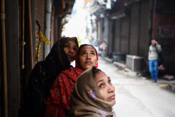 Le donne guardano la fabbrica in cui un giorno prima è scoppiato un incendio, nell'area di Anaj Mandi a Nuova Delhi, il 9 dicembre 2019 - Sputnik Italia
