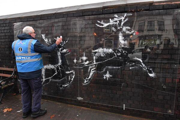 Un addetto pulisce un'opera d'arte dell'artista britannico Banksy, Birmingham, il 10 dicembre 2019 - Sputnik Italia