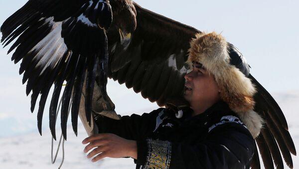 Un cacciatore tiene la sua aquila durante una tradizionale competizione di caccia nei pressi del villaggio di Kainar nella regione di Almaty, Kazakistan - Sputnik Italia