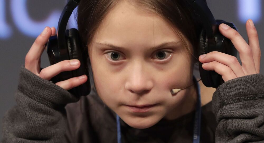 Climate activist Greta Thunberg adjusts the headphones during a press conference in Madrid, Friday Dec. 6, 2019