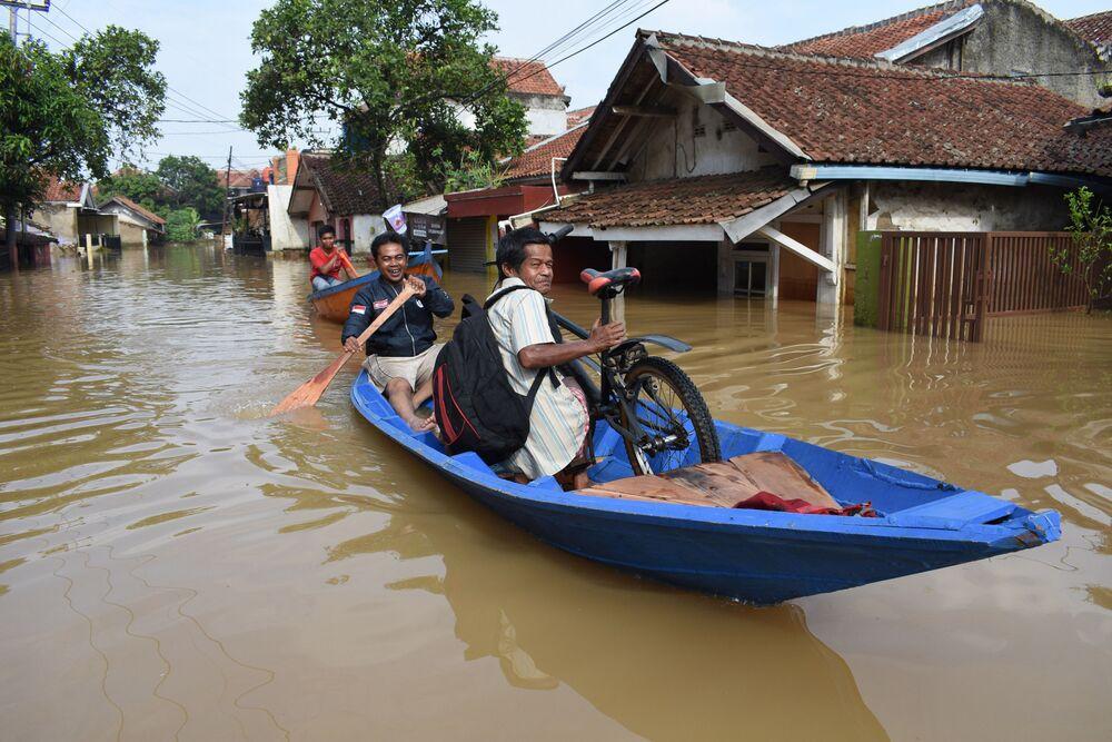 Abitanti si spostano in barca attraverso una strada allagata a Dayeuhkolot,  Indonesia, il 18 dicembre 2019