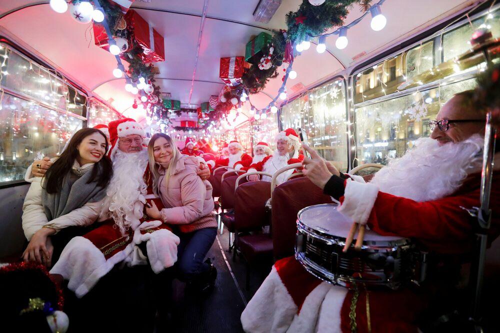 Musicisti vestiti da Babbo Natale in un autobus a San Pietroburgo.