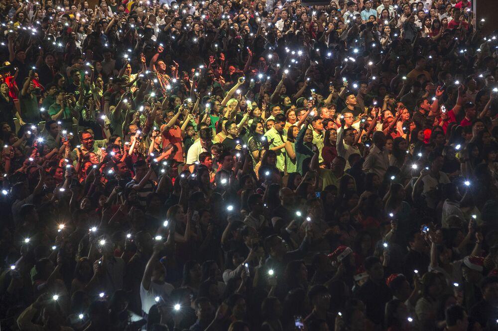 I cristiani si fanno luce con i telefonini durante una messa di Natale in Indonesia.
