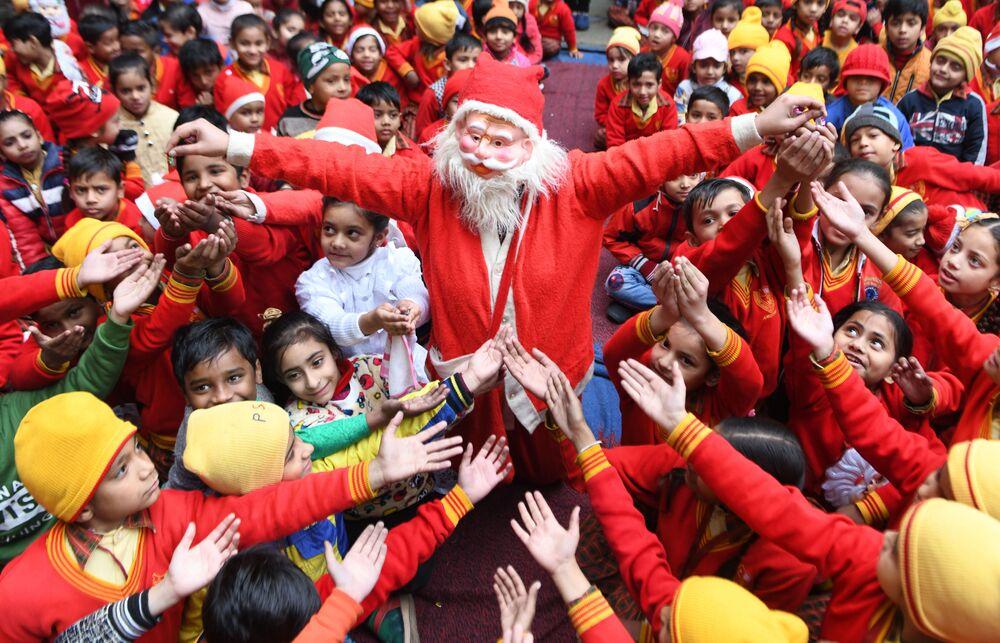 Una ragazza vestita da Babbo Natale distribuisce i regali ai bambini in India.