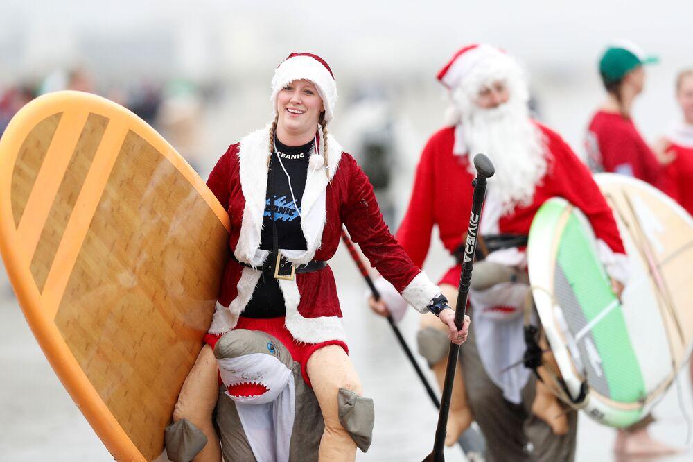 I partecipanti alla nuotata annuale dei surfer vestiti da Santa Claus negli USA.