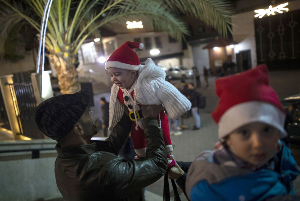 Un uomo gioca con il bambino prima della messa natalizia nella Striscia di Gaza.