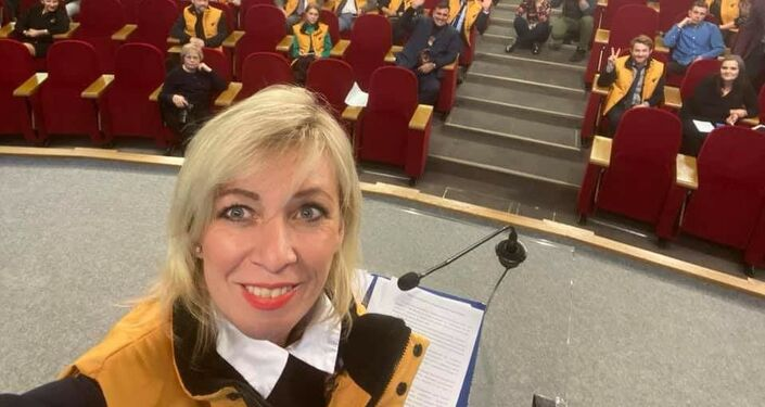 Selfie di Maria Zakharova vestita con una giacchetta gialla