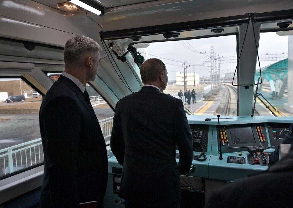 Il presidente russo Vladimir Putin nella cabina di guida del treno che parte per la prima volta sul ponte di Crimea