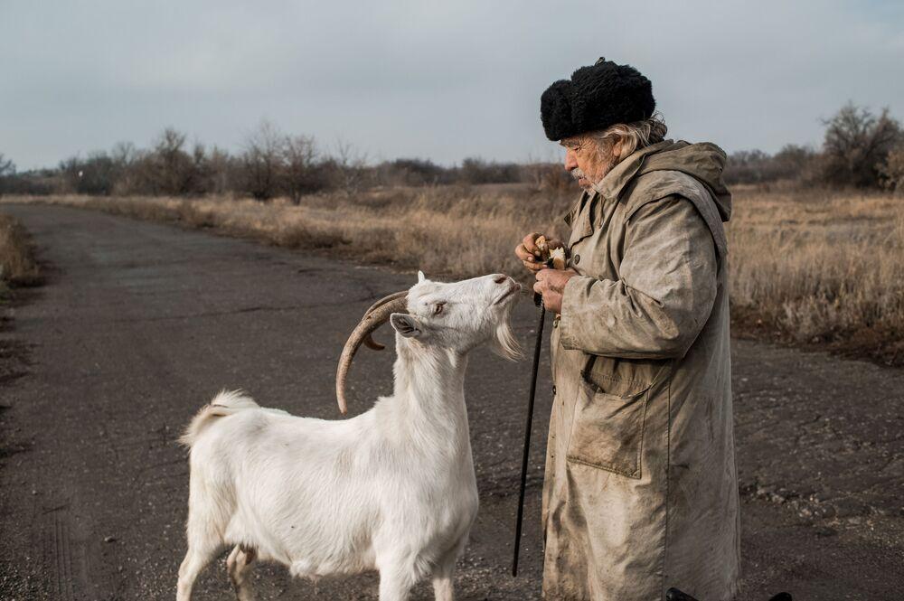 Un uomo nutre una capra nel villaggio di Donetsky