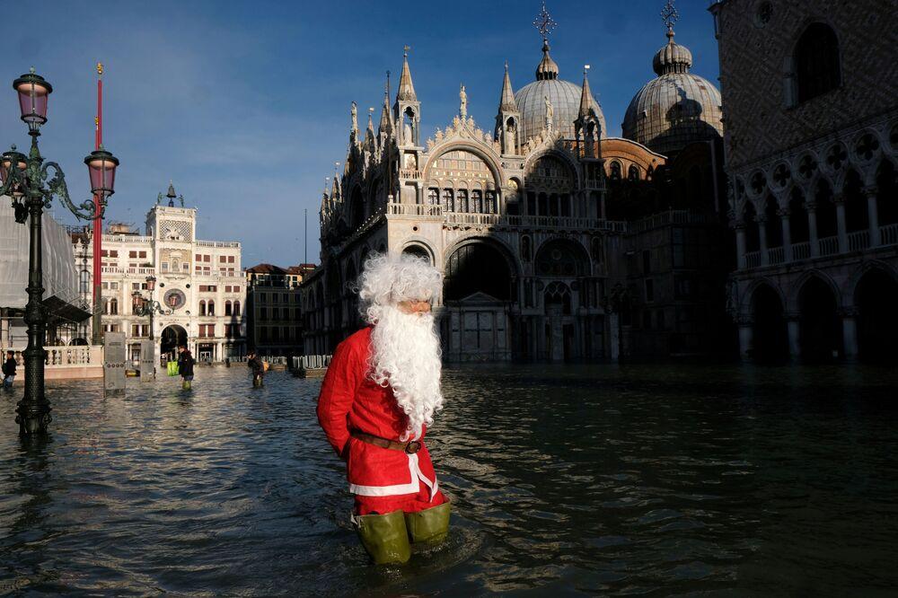 Un uomo vestito da Babbo Natale durante l'acqua alta a Venezia, Italia, il 23 dicembre 2019