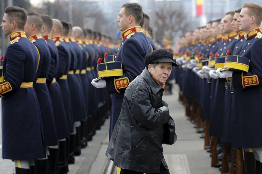 Una donna cammina tra i soldati di guardia d'onore durante un servizio commemorativo nel cimitero degli Eroi a Bucarest, Romania